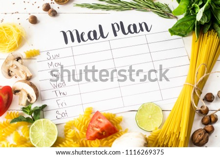 A meal plan for a week on a white table among products for cooking - pastas, basil, vegetables, lime, seeds, nuts and spices. Top view, flat lay, copyspace #1116269375