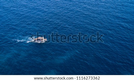 Aerial view of a small boat that runs on the blue waters of the Tyrrhenian Sea off the coast of Italy. The boat floats without problems on the calm and flat sea  #1116273362