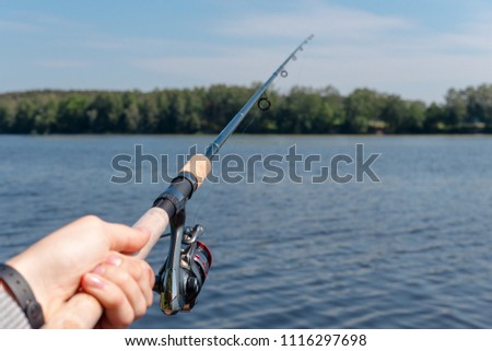 men's hand holding spinning and fishing #1116297698