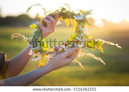 Midsummer in Latvia: celebration of Ligo - a young woman weave a wreath and collect field flowers #1116362255