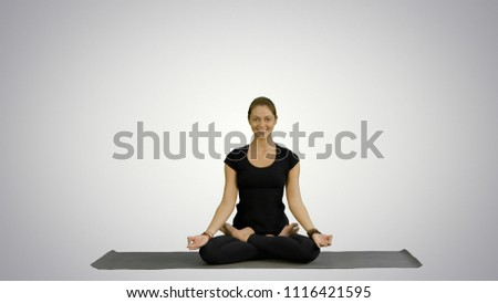Young woman meditates while practicing yoga on white background