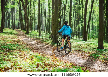 young woman ride bicycle in forest by trail #1116509393