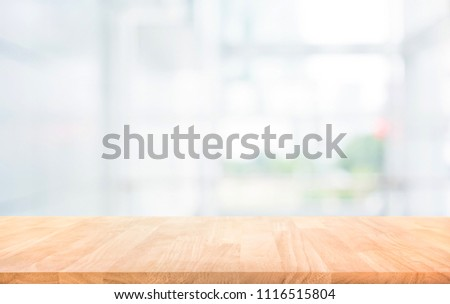 Wood table top on blur white glass wall background form office building.For montage product display and design key visual layout #1116515804