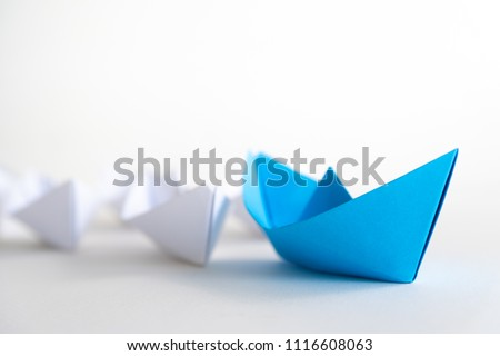 Leadership concept. blue paper ship lead among white. One leader ship leads other ships. #1116608063