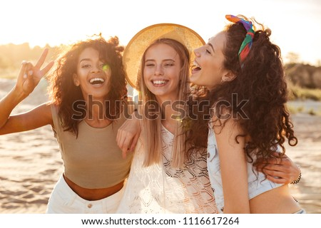Image of three joyous multiethnic girls 20s in stylish clothing laughing and showing peace sign at camera during beach party at seaside #1116617264