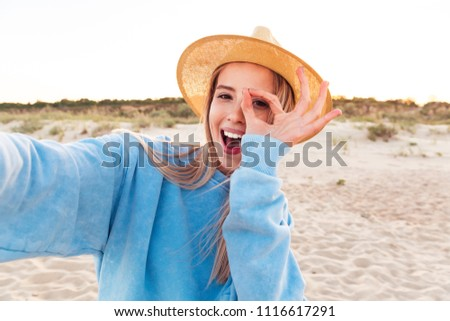 Close up of lovely young girl in summer hat taking a selfie and showing ok gesture at the beach