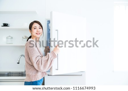 Young woman opening a door of a refrigerator. #1116674993