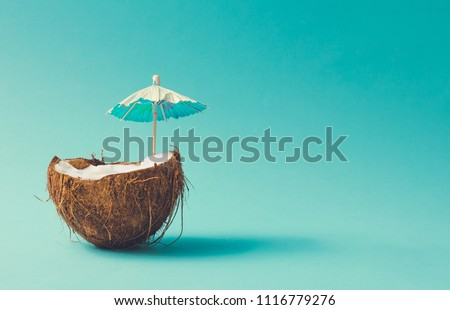 Tropical beach concept made of coconut fruit and sun umbrella. Creative minimal summer idea. #1116779276
