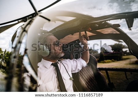 Pilot with headset starting the controls in the private helicopter. Helicopter pilot sitting in the cockpit. #1116857189