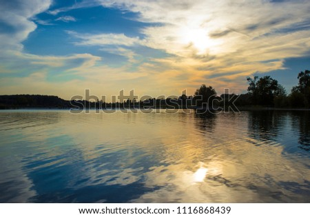 Beautiful sunset, sunrise and reflection of the sky with clouds in the water in river Drava, Varaždin, Croatia #1116868439