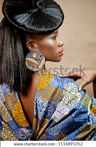 Rear view of a beautiful young African woman with an exotic hairstyle wearing stylish jewelry and clothing standing against a brown background #1116895352