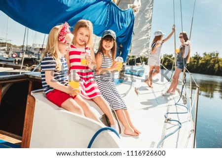 The children on board of sea yacht drinking orange juice. The teen or child girls against blue sky outdoor. Colorful clothes. Kids fashion, sunny summer, river and holidays concepts. #1116926600