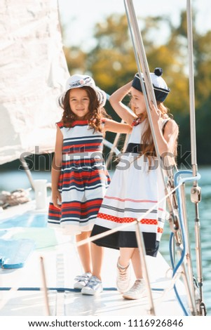 The children on board of sea yacht drinking orange juice. The teen or child girls against blue sky outdoor. Colorful clothes. Kids fashion, sunny summer, river and holidays concepts. #1116926846