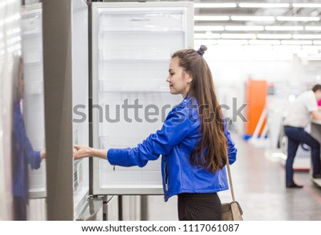 beautiful young girl in a supermarket shopping. chooses appliances for home: stove and refrigerator #1117061087