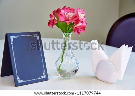 On the table is a blue nameplate, vase with fresh lilies and napkins.
