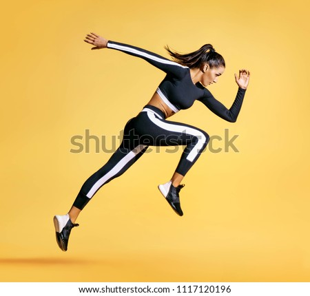 Sporty woman runner in silhouette on yellow background. Photo of attractive woman in fashionable sportswear. Dynamic movement. Side view. Sport and healthy lifestyle #1117120196