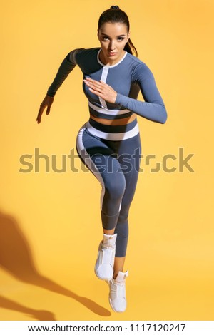 Beautiful woman runner in silhouette on yellow background. Photo of sporty woman in fashionable sportswear. Dynamic movement. Strength and motivation. Full length #1117120247