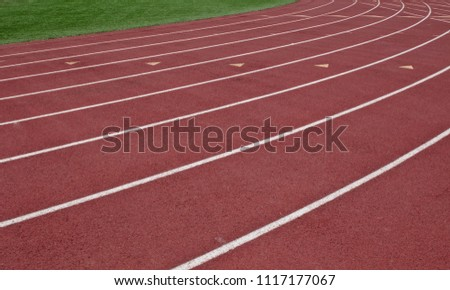 White painted running lanes on a red track with green grass #1117177067