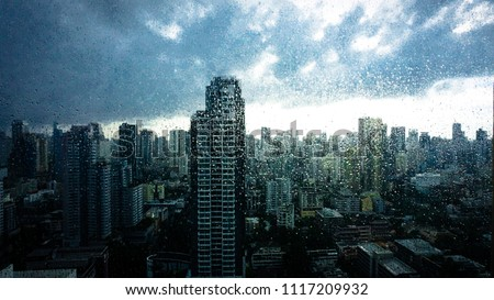 Rainy season, Rain drops on window's glass is viewing the downtown city skyline on a dark weather day. Abstract rain drop/raining scenery background - can be used for display or montage your products. #1117209932