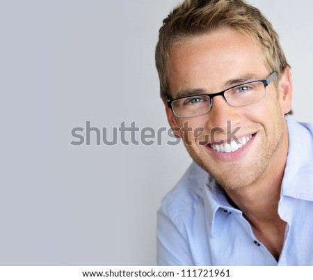 Young handsome man with great smile wearing fashion eyeglasses against neutral background with lots of copy space #111721961