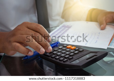 man pressing calculator for business finance on car showroom blurry background.for automotive or transportation #1117318883