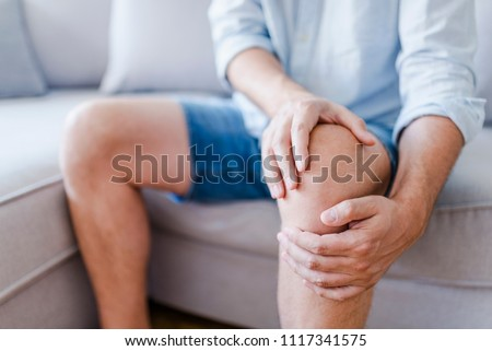 Man suffering from knee pain sitting sofa. A mature man massaging his painful knee. Man suffering from knee pain at home, closeup. Pain knee  #1117341575