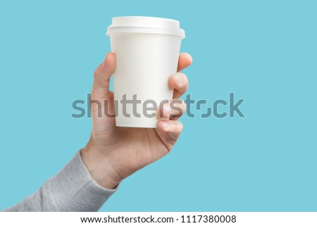 A paper cup of coffee in the hand. White paper cup of coffee in hand. For mock up. Isolated. On colored background #1117380008