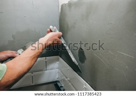 Man is putting white tiles on the grey concrete. Maintenance repair works renovation in the flat. Restoration indoors. Man is priming a surface with a brush and palett knife. #1117385423