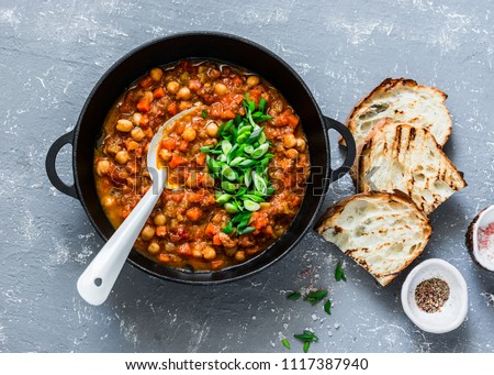 Vegetarian mushrooms chickpea stew in a iron pan and rustic grilled bread on a gray background, top view. Healthy vegetarian food concept. Vegetarian chili #1117387940