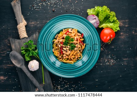 Pasta with mushrooms and vegetables. Italian cuisine. On a wooden background. Top view. Copy space. #1117478444