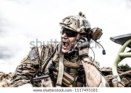 Special forces soldier, military communications operator or maintainer in helmet and glasses, screaming in radio during battle in desert. Calling up reinforcements, reporting situation on battlefield Royalty-Free Stock Photo #1117495181