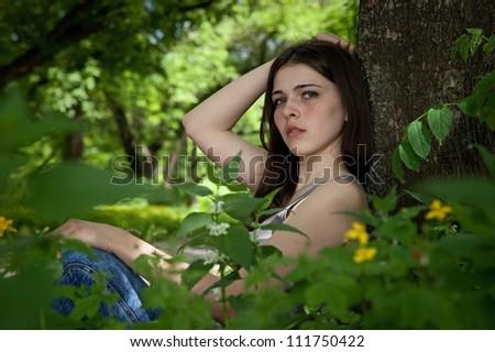 attractive girl sitting near tree. outdoor shot #111750422