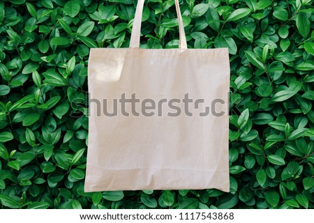Blank White Mockup Linen Cotton Tote Bag on Green Bush Trees Foliage Background. Eco Nature Friendly Style. Environmental Conservation Recycling Concept. Template for Artwork Text. Japanese #1117543868