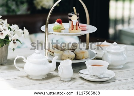 Traditional English afternoon tea: scones with clotted cream and jam, strawberries, with various sandwiches on the background Royalty-Free Stock Photo #1117585868