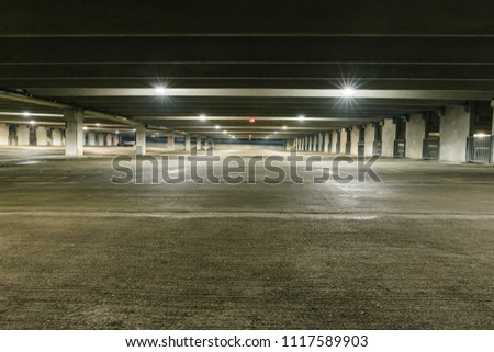Grungy, dimly lit empty parking garage with overhead lights and an exit sign hanging from the ceiling. #1117589903