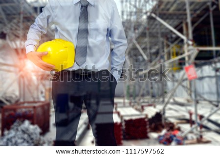 Engineer or Safety officer holding hard hat with blurred construction site background.. #1117597562
