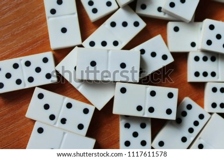 White dominoes, dots of black color. Lies on a brown wooden table. Background in blur. #1117611578