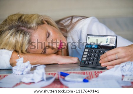 attractive worried and desperate blond woman calculating domestic money expenses doing paperwork and bank bills accounting with calculator suffering stress in financial problem and depression #1117649141