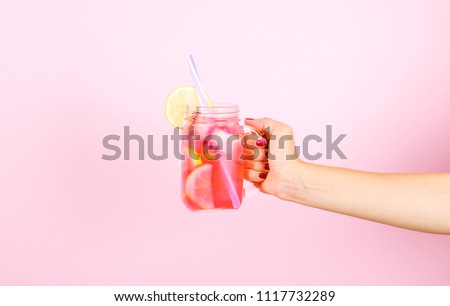 Young woman hands holding freshly squeezed strawberry lemonade of citrus fruits. Female with mason jar full of cold cocktail, lemon, orange, lime & mint leaves. Pink background, copy space, close up. #1117732289