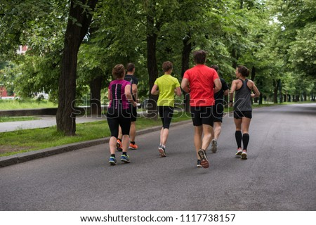 group of healthy people jogging in city park, runners team on morning training #1117738157
