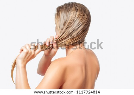 Hair care concept. Blond woman with long wet hair is applying hair conditioner #1117924814
