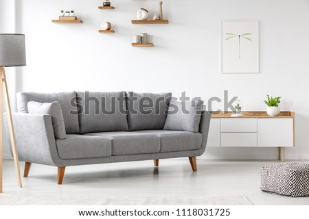 Simple, gray sofa standing next to a white cupboard in living room interior with decorations on wooden shelves. Real photo #1118031725