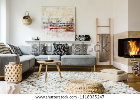 Wooden table next to grey corner settee in warm living room interior with painting and fireplace. Real photo #1118035247