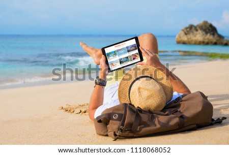 Man reading travel blog on beach #1118068052