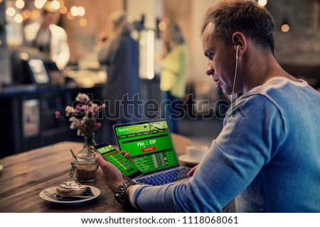 Man using online sports betting services on phone and laptop Royalty-Free Stock Photo #1118068061