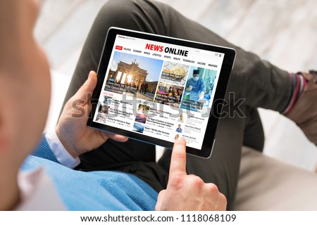 Man reading daily news online on tablet Royalty-Free Stock Photo #1118068109
