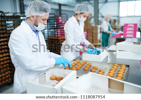 Confectionery factory employees in white coats collecting freshly baked pastry from tray and putting it into paper boxes. #1118087954