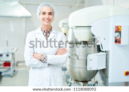 Beautiful confectionery factory worker standing in white coat with arms crossed smiling and looking at camera. Royalty-Free Stock Photo #1118088092