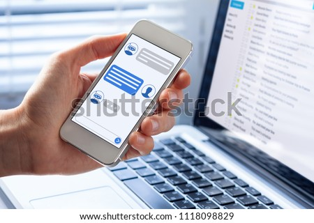 Chatbot conversation on smartphone screen app interface with artificial intelligence technology providing virtual assistant customer support and information, person hand holding mobile phone #1118098829