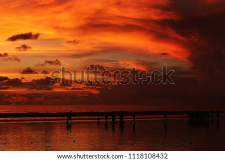 Gorgeous red and yellow Indian ocean sunset at Seminyak beach in Bali Indonesia with people near the sea #1118108432